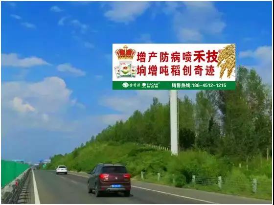 """""""增产防病喷禾技,垧增吨稻创奇迹""""的高速公路旁广告牌"""